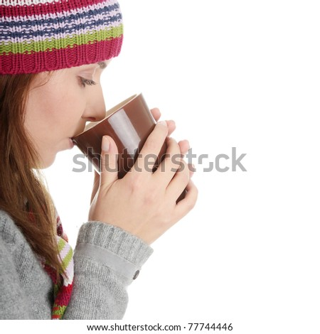 Young woman in winter hat with cup of hot chocolate or coffee or tea - stock photo