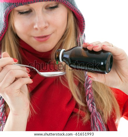 young woman in winter hat with spoon of syrup - stock photo