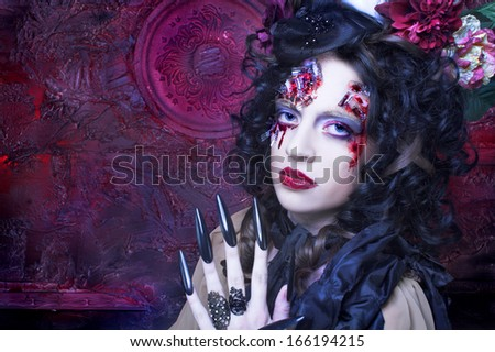 Young woman in witch image with bloody makeup ann with skull.