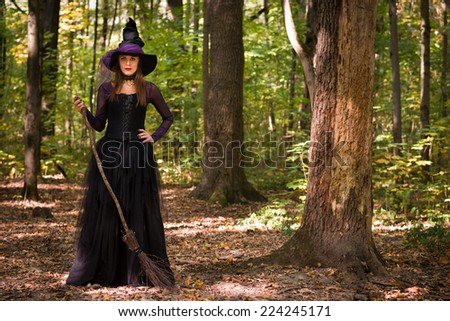 young woman in witch's hat holding broom and looking at camera