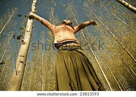 Young woman in woods feeling freedom - stock photo