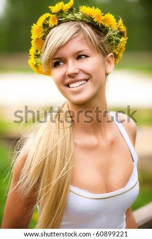 Young woman in wreath from yellow dandelions. - stock photo