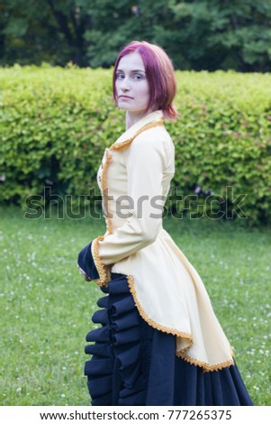 Young woman in yellow and black historical dress standing in the park