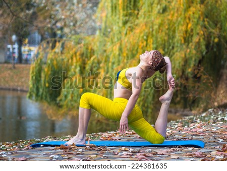Young woman in yellow clothing doing yoga in the autumn Park near lake