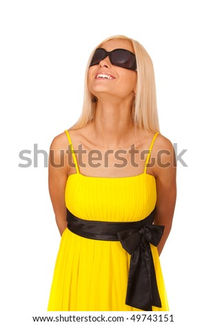 Young woman in yellow dress and sun glasses looks upwards and smiles, it is isolated on white background.