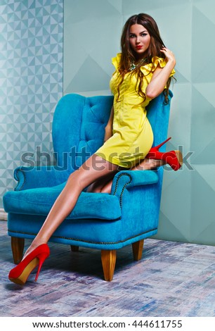 Young woman in yellow dress in modern interior on blue chair - stock photo