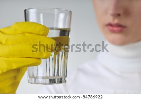Young woman in yellow hygienic gloves holding glass of water - concentration