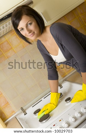 Young woman in yellow rubber gloves cleaning cooker. Looking at camera. Front view. - stock photo