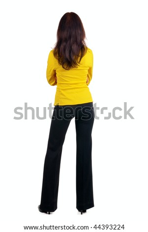 Young woman in yellow suit looking at wall. The rear view.