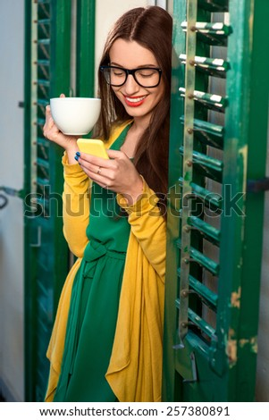Young woman in yellow sweater and a cup of coffee using mobile phone on the balcony with window shutters in old building. - stock photo