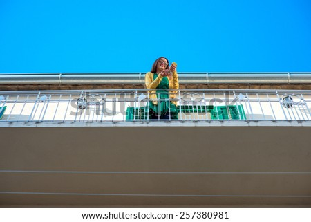 Young woman in yellow sweater and glasses using mobile phone on the balcony with window shutters in old building. General plan.  - stock photo