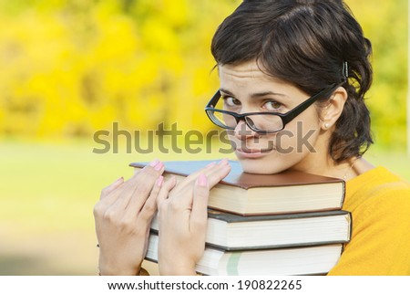 Young woman in yellow sweater holds three books in hands. - stock photo