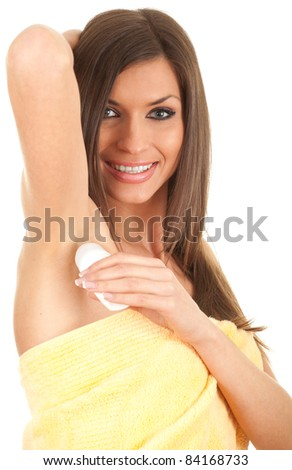 young woman in yellow towel using an antiperspirant - stock photo
