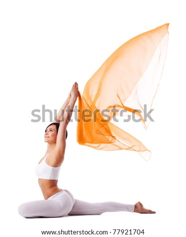 Young woman in yoga pose and flying fabric - stock photo