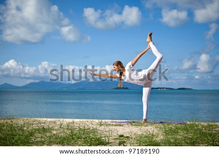 Young woman in yoga pose on the beach - stock photo