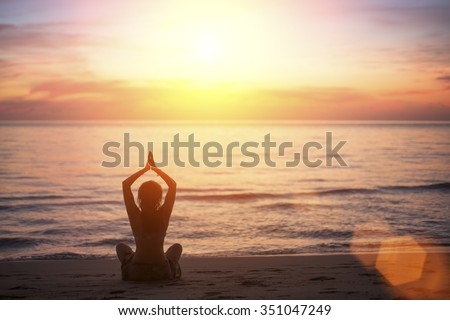 Young woman in yoga pose on the beach during the amazing sunset.