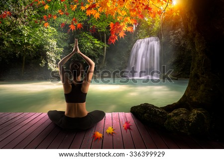 Young woman in yoga pose sitting near waterfall, Rear view, Yoga is a physical, mental, and spiritual practice or discipline which originated in India, Yoga exercise and meditation with nature concept