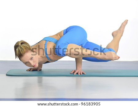 Young woman in yoga pose standing on hands with her body in the air. - stock photo