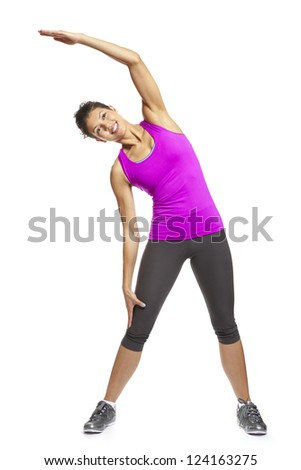 Young woman in yoga pose wearing sports outfit smiling on white background - stock photo