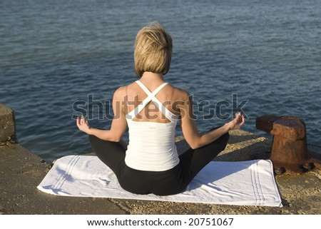 Young woman in yoga position meditates next to the sea - stock photo