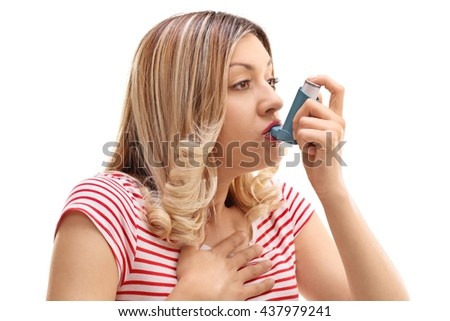 Young woman inhaling her asthma medication isolated on white background - stock photo