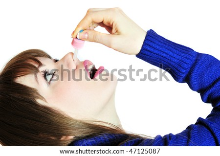 young woman injecting drops into the nose - stock photo