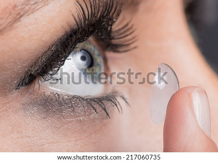 Young woman Inserting a contact lens, close-up - stock photo