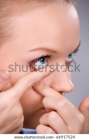 Young woman Inserting a contact lens closeup