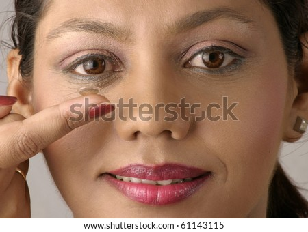 Young woman inserting a contact lens in her eye, close-up - stock photo