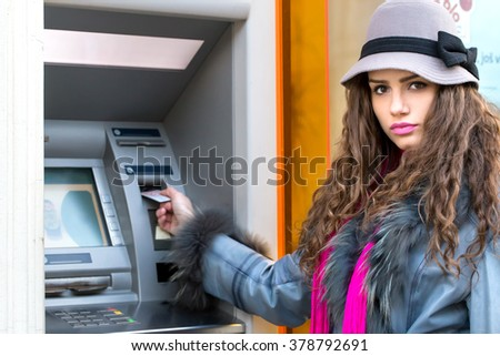 young woman inserting a credit card to ATM - stock photo