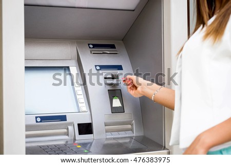 young woman inserting a credit card to ATM