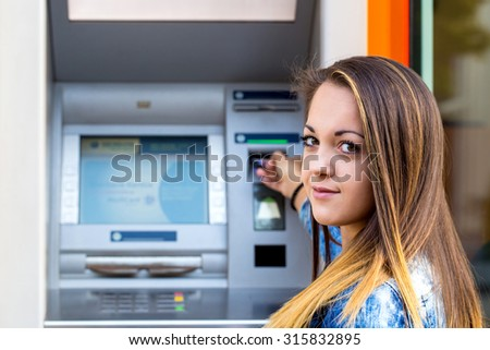 young woman inserting credit card at ATM - stock photo