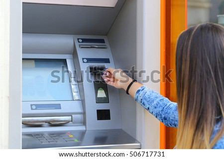 young woman inserting credit card at ATM