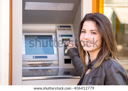 young woman inserting credit card to ATM - stock photo
