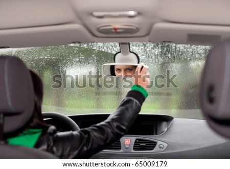 young woman inside car setting mirror regulates