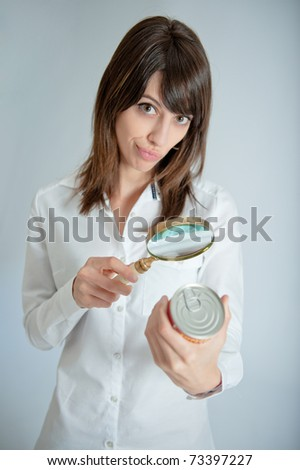 Young woman inspecting a can?s nutrition label with a magnifying glass - stock photo