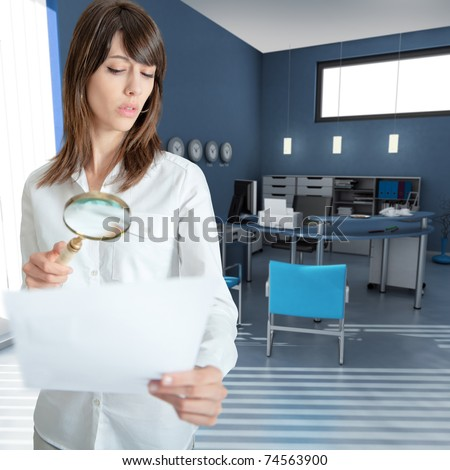Young woman inspecting a document through a magnifying glass in an office - stock photo