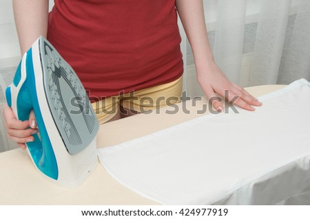 Young woman ironing clothes, housework