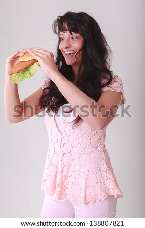 Young woman is a bun topped with Wiener schnitzel and salad / Perfect Schnitzelsemmel - stock photo