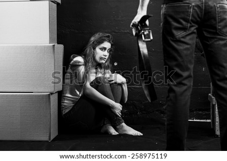 Young woman is a victim of domestic violence and abuse siting on the floor is scared of man with belt on black-and- white background - stock photo
