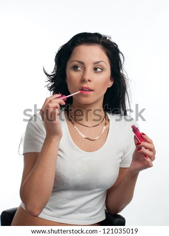young woman is applying lipgloss on the white background