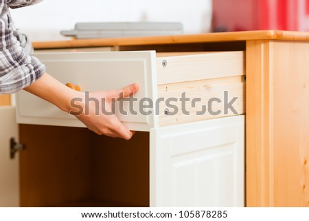 Young woman is assembling a cupboard because she is moving in or out - only hand to be seen