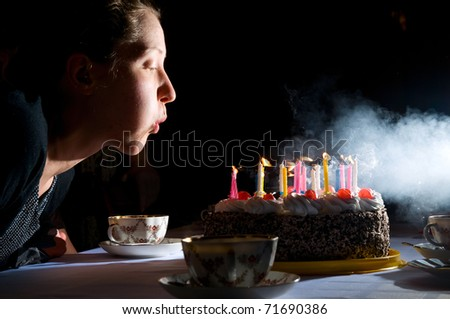 young woman is blowing out candles on cake - stock photo