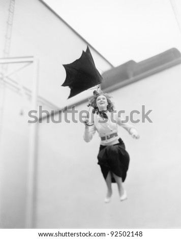 Young woman is blown away, jumping from a roof with an umbrella - stock photo