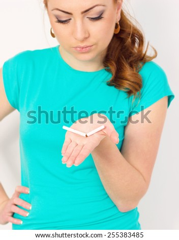 Young woman is breaking a cigarette, quit smoking concept - stock photo