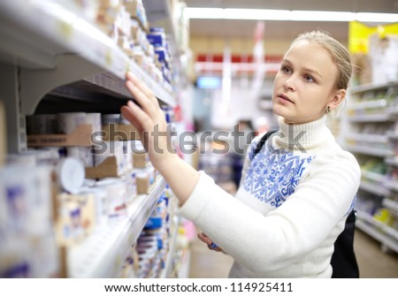 Young woman is choosing food for her child in the supermarket.