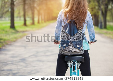 Young woman is cycling into the sunset in the park - stock photo