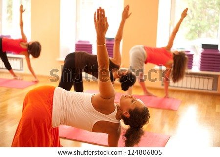 Young woman is doing yoga at health club - stock photo