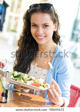 Young woman is eating mixed vegetable salad in cafe - stock photo