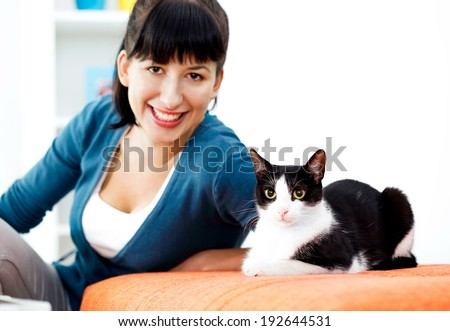 Young woman is enjoying living room with cat. - stock photo